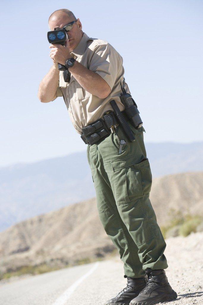 Enforcer using radar gun on a highway