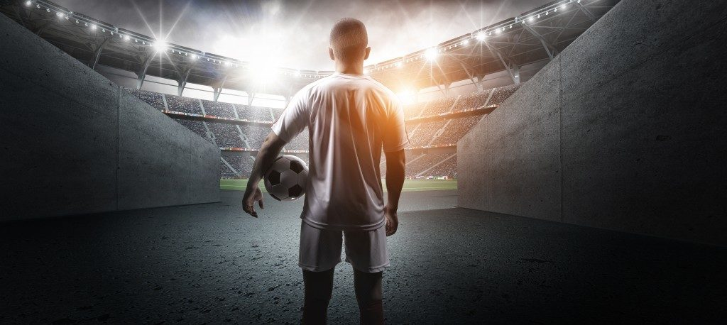 soccer player entering the grand football field